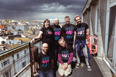 ex mindout volunteers stand on a balcony with dramatic clouds in the background